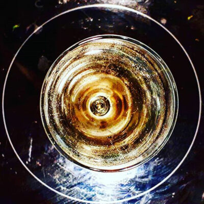 glass with sparkling wine on ceramic hob.